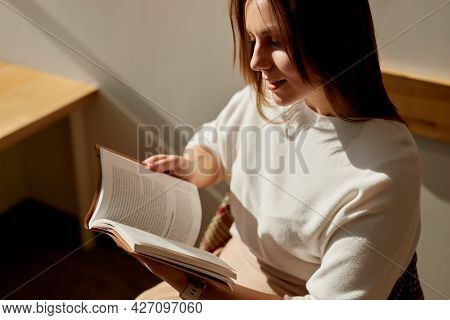 Positive Young Female Enjoying New Novel While Reading Book In Sunny Room During Free Time At Home