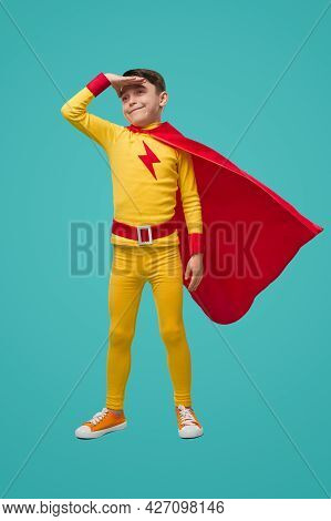 Full Body Of Determined Little Boy In Superhero Costume With Red Cape Keeping Hand Near Forehead And