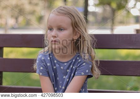 Little Cute Girl Blonde Six Years Old Sits In The Park On A Bench And Dreams, Portrait Of A Preschoo