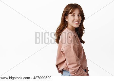Wellbeing And People Concept. Portrait Of Young Smiling Redhead Woman Turn Head At Camera, Stands In