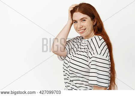 Natural Beauty. Girl With Red Hair And Freckles, Touch Her Head, Smiling Happy And Gazing At Camera,