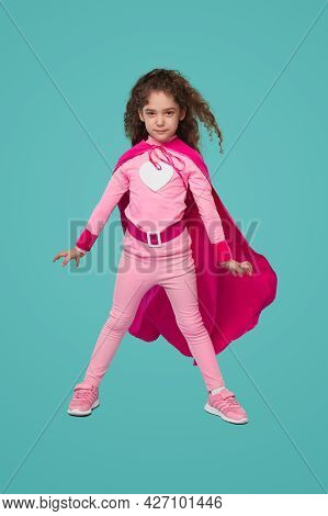Full Body Of Courageous Little Curly Haired Girl In Pink Superhero Costume With Heart Sign Looking A