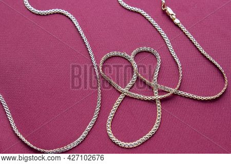 Gold Chain On A Red Background Close-up. Jewelry Is Great For A Gift