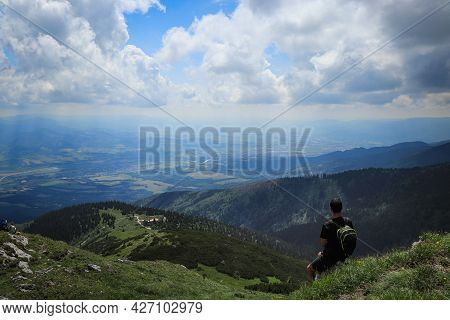 Athlete In A Black T-shirt Sits On Top Of Mala Fatra Mountain. Hiker Walks Along Ridges Of Lesser Fa