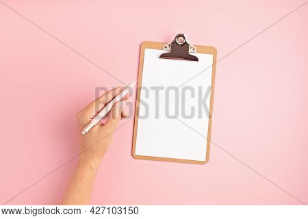 Woman Left Hand With Pen And Empty Clipboard. International Left Handers Day Concept.