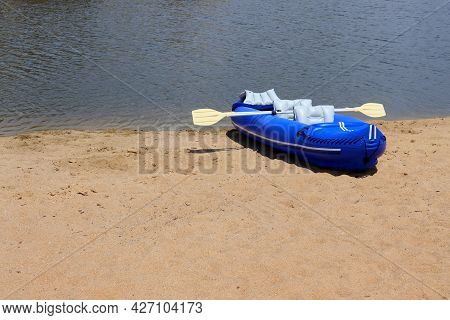 Blue Rubber Boat And Oars On The Sandy Bank Of The River. Inflatable Boat, Side View.