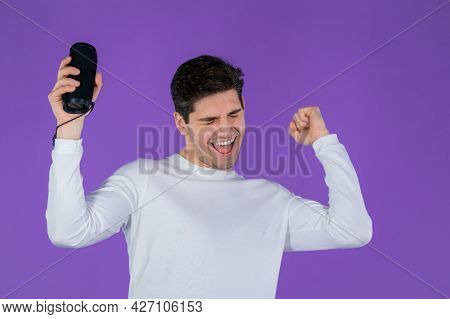 Man Listening To Music By Wireless Portable Speaker - Modern Sound System. Young Guy Dancing, Enjoyi