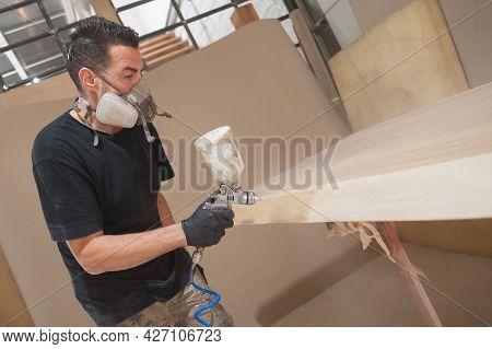 Man In Respirator Mask Painting Wooden Planks At Workshop. Craftsman Modern Furniture Factory Paint