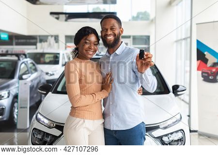 Happy Owners. Cheerful Black Spouses Holding Key Of Their New Car