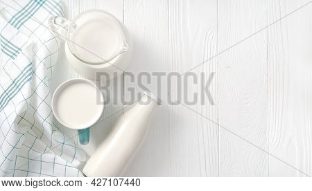 Milk In Mug And Jug Of Milk And Napkin On White Wooden Table. Top View Flat Lay. Bottle Of Milk On W