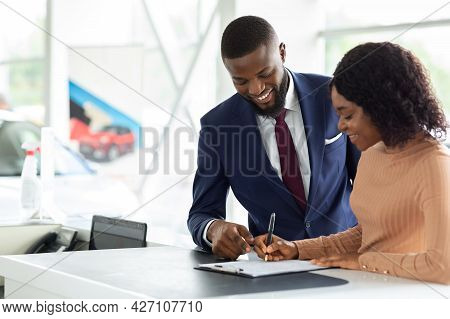 Black Woman Buying New Car, Signing Papers With Salesman In Dealership Office