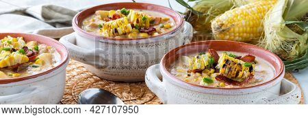 Narrow View Of Three Bowls Of Chicken And Corn Chowder Topped With Grilled Corn And Bacon, Ready For