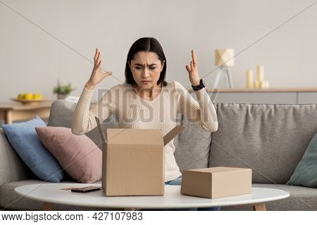 Angry, Unhappy, Confused Millennial Arab Woman Unpacking Parcel, Wrong Or Broken, Online Store Order