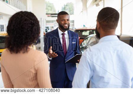 Portrait Of Handsome Black Salesman Consulting Clients In Modern Car Dealership Center