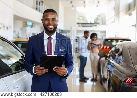 Handsome Black Car Salesman In Suit Posing At Workplace In Auto Showroom