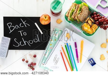 Top Down View Of Various School Supplies, A Lunch Kit And A Black Chalkboard With The Words Back To