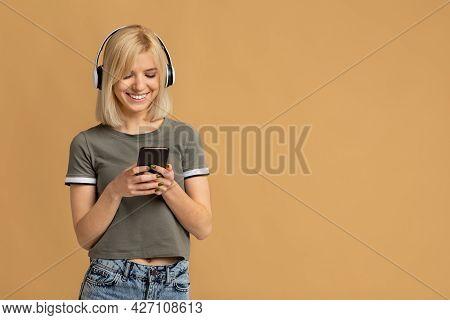 Calm Happy Lady Wearing Wireless Headphones And Using Smartphone, Enjoying Favorite Audio Playlist,