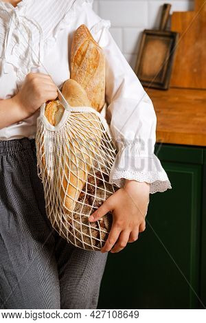 1 Woman In A White Blouse With Bread In A Bag In The Kitchen