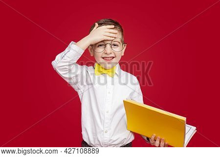 Exhausted Little Student Looking At Camera With Smile And Wiping Sweat From Forehead While Reading T