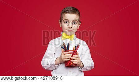 Clever Boy In School Uniform And Glasses Carrying Cup With Pencils And Looking At Camera During Stud