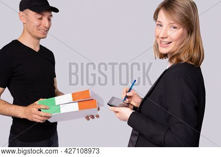 The Courier In A Black Uniform With A Peaked Cap Delivers Two Boxes For A Smiling Woman And She Sign