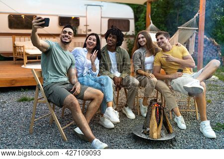Diverse Young Friends Taking Selfie Near Campfire In Evening, Using Smartphone, Sitting Next To Rv D