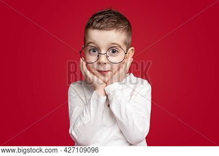 Cute Smart Little Nerd Kid In Spectacles Keeping Hands Near Cheeks And Looking With Amazement At Cam