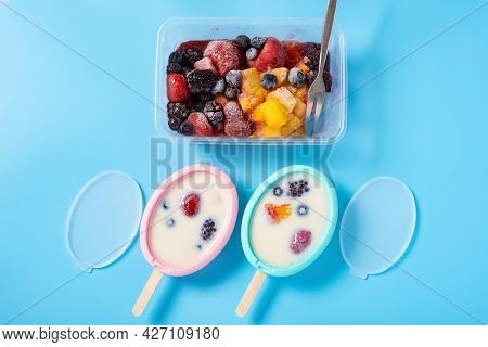 Two Homemade Milk Popsicles With Various Fruit Slices