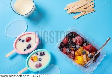 Preparing Milk Popsicle With Various Fruit Slices