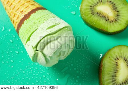 Top View Fresh Kiwi Fruit Slices And A Kiwi Fruit Flavor Ice Cream Cone On Green Background