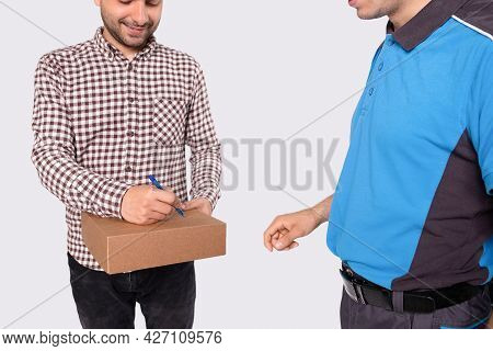 The Courier In Blue Uniform Delivered The Brown Box For The Man In Checkered Shirt And He Is Signing
