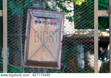 An Old Rusty Mailbox Hangs Crookedly From A Wire Mesh Fence. Several Coats Of Partially Peeling Pain