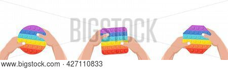 Hands Holding An Anti-stress Toy - Pop It. Hand Toy Of Different Shapes In Rainbow Color With Rubber