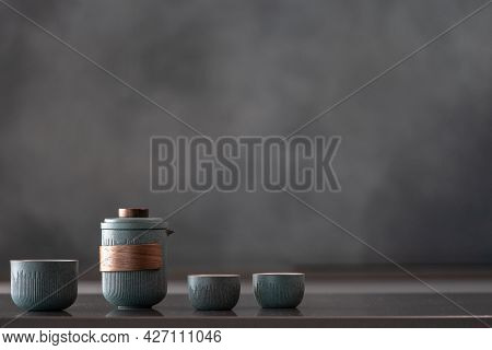 Glossy Reflective Countertop With Nice Ceramic Blue Teapot Set, Three Small Cups, Brewing Tea For Gu