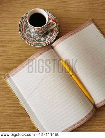 Writing Paper, A Cup Of Coffee And A Pen Resting On A Notepad On A Wooden Desk