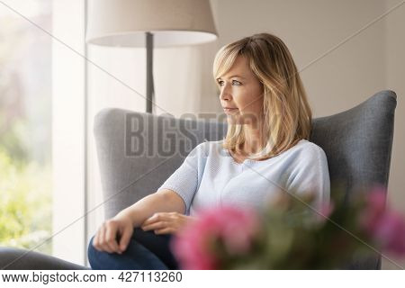 Shot Of Attractive Middle Aged Woman Daydreaming While Relaxing On An Armchair At Home.