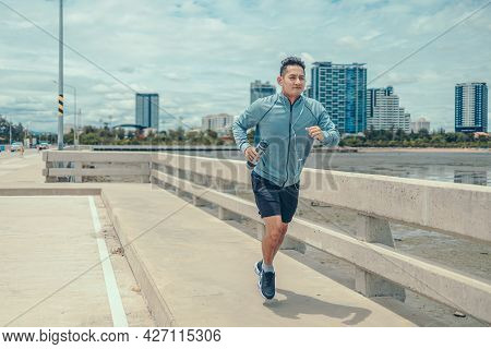 Young Sport Man Hold Water Bottle And Wearing Earphone While Jogging And Running On The Road And Cit