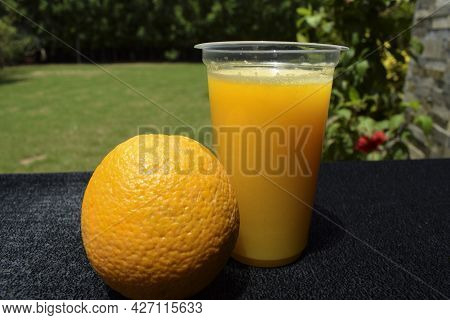Citrus Malta Juice Served In Transparent Glass With Malta Fruit On Table. Nature Background Open Are