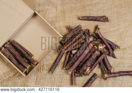 Pet Treat And Cardboard Box On Burlap Fabric. Dried Dog Goodies. Delicious Red Beef Gullet Sticks. B