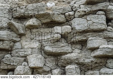 An Old Fortress Wall Made Of Gray Stones Of Random Shapes And Sizes. The Texture Of The Gray Fortifi