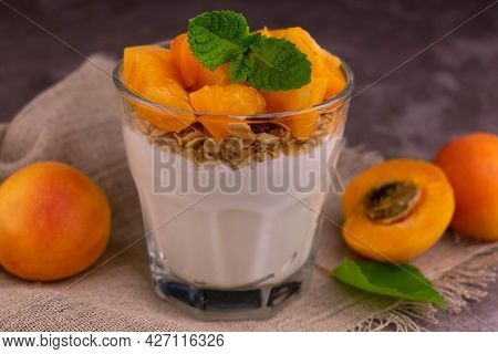 Apricot Yogurt With Muesli In A Glass On A Gray Background. Close-up.