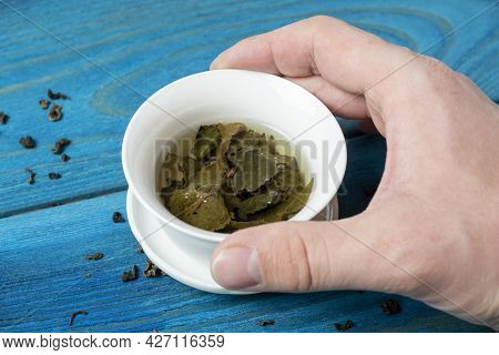 A Woman's Hand Holds A White Porcelain Bowl With Tea. Blue Wooden Background. The Opened Leaves Of L