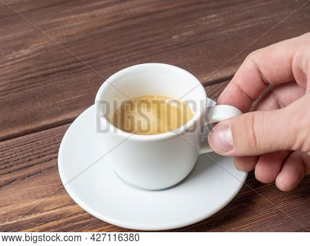 Close-up Of A Man's Hand Holding A Small White Cup Of Aromatic Espresso Over A White Saucer. Wooden