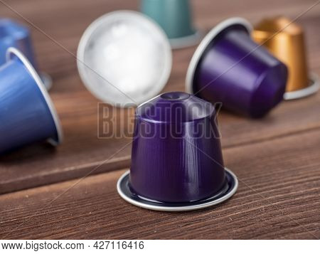 Bright Multi-colored Capsules With Coffee On A Brown Wooden Background. Close Up, Side View