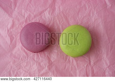 Multicolored Macaroons On A Pink Paper Background. Top View, Flat Lay.. Sweet And Delicious Dessert