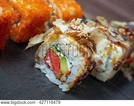 Close-up Of A Sushi Roll On A Black Plate. Traditional Japanese Cuisine
