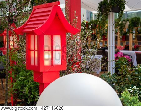 A Cafe Decorated With A Red Street Lamp And Flowers. Focus On Flowers
