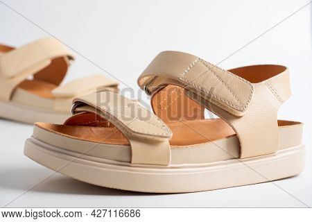 Close-up Of Beige Leather Sandals On A White Background. Pair Of Shoes, Women's Flight Shoes