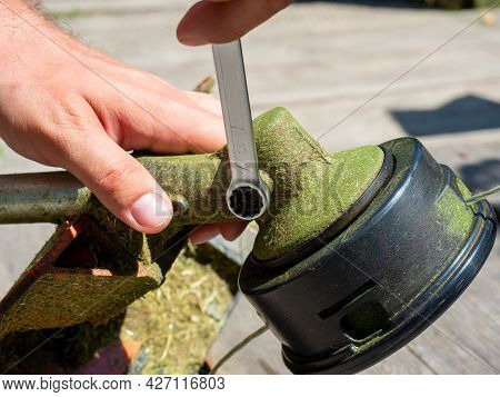 Close-up Of A Grass Mowing Trimmer, The Screw On The Gearbox Is Unscrewed With A Wrench. Maintenance