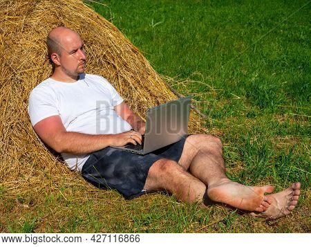 A Middle-aged Man Dressed In A T-shirt And Shorts Is Lying On A Yellow Haystack With A Laptop In His